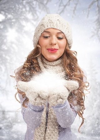 Christmas woman blowing snow, against winter forest photo