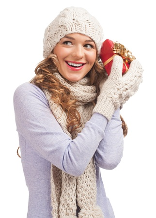 Happy young woman wearing knitted cap, scarf and mittens holding Christmas gift box  photo