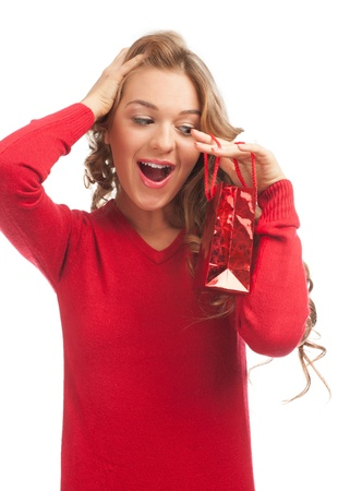 Pretty excited woman with christmas gift. Happy surprised woman with gift bag.  photo