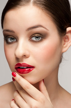 Close-up portrait of young beautiful woman with red lipstick and manicure photo