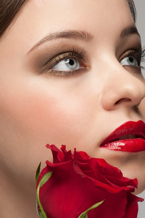Close-up portrait of young beautiful woman with red rose and stylish bright make-up photo
