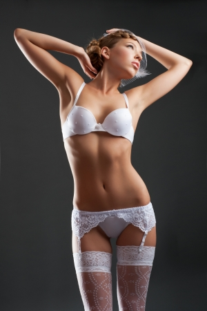 Portrait of a sensual bride wearing white lingerie and white veil photo