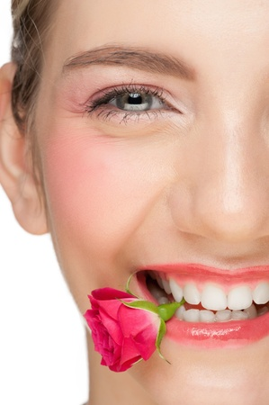 Close-up portrait of young beautiful woman with pink make-up holding pink rose bud in her mouth photo