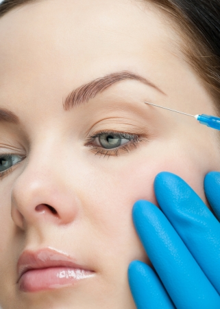 Cosmetic injection of botox to the pretty female face. Injecting to the eye. photo