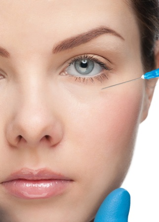 Cosmetic injection of botox to the pretty female face. Isolated on white background Stock Photo