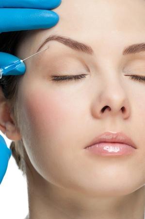 ojos cerrados: La inyecci�n de botox cosm�tico a la cara de mujer bonita. Aislado sobre fondo blanco Foto de archivo