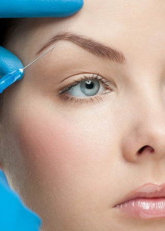 Cosmetic injection of botox to the pretty female face photo
