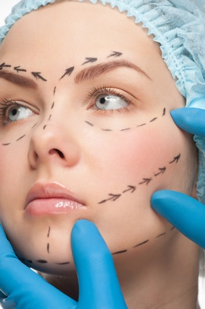 Beautiful young woman with perforation lines on her face before plastic surgery operation. Beautician touching woman face. Stock Photo - 11955267