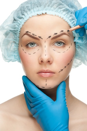 Beautiful young woman with perforation lines on her face before plastic surgery operation. Beautician touching woman face. photo
