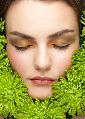 Close-up portrait of young beautiful woman face with stylish makeup surrounded green flowers Stock Photo - 11955316