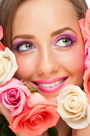 Portrait of sensual beautiful woman with roses and stylish bright make-up smiling photo