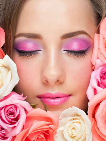 Close-up portrait of sensual beautiful woman with stylish bright make-up. Young woman with closed eyes surrounded by roses