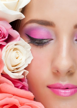 Close-up portrait of sensual beautiful woman with roses and stylish bright make-up  photo
