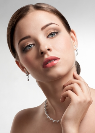 Portrait of beautiful woman with beautiful make-up and hairstyle. Elegant woman with pearl jewelry photo