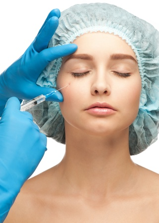 Close-up shot of cosmetic injection of botox to the pretty female face. Isolated on white background photo