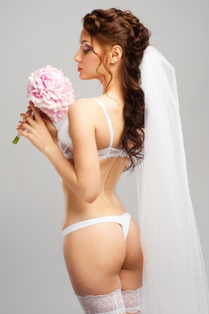 Portrait of a sensual bride wearing white lingerie and white veil with bouquet of peonies photo