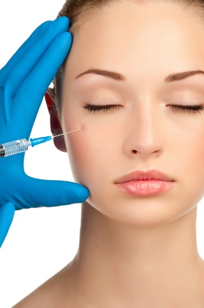 Cosmetic injection of botox to the pretty female face. Isolated on white background Stock Photo - 12794971