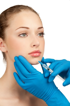 plastic glove: Cosmetic injection of botox to the pretty female face. Isolated on white background Stock Photo