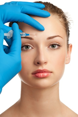 cosmetic surgery: Cosmetic injection of botox to the pretty female face. Isolated on white background Stock Photo