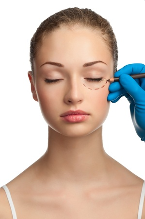 Beautician drawing perforation lines on woman face before plastic surgery operation Stock Photo - 12794901