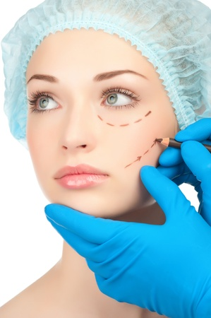 Beautician drawing perforation lines on woman face before plastic surgery operation Stock Photo - 12794957