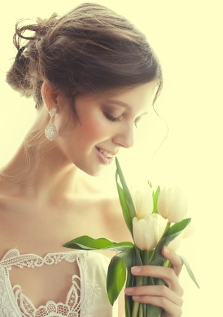 Portrait of young beautiful woman with bouquet of white tulips  photo