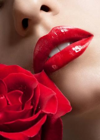 赤い口紅と美しい赤いバラとセクシーな女性の唇のクローズ アップ ショット