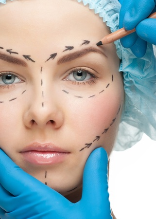 Beautiful young woman with perforation lines on her face before plastic surgery operation. Beautician touching woman face. Imagens