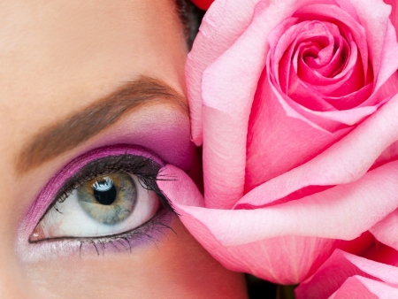 Close-up of woman eye with bright stylish makeup and pink roses photo