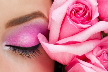 Close-up of closed woman eye with bright stylish makeup and pink roses photo