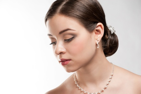 Portrait of lovely woman with beautiful make-up and hairstyle. Elegant woman with pearl jewelry photo