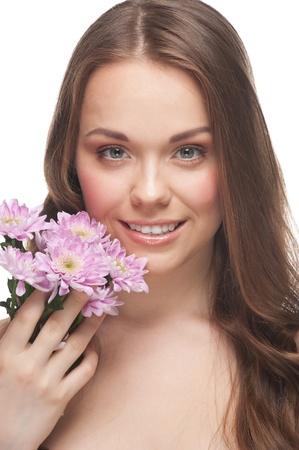 Pretty young woman with beautiful make-up and perfect healthy skin with flowers photo
