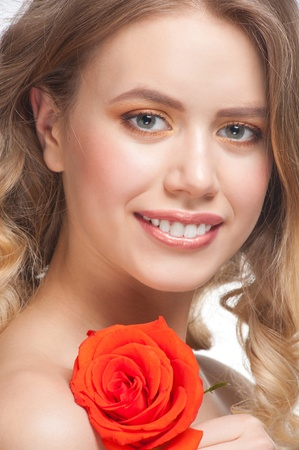 Pretty young woman with beautiful make-up and perfect healthy skin with rose in her hand photo