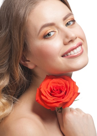 Pretty young woman with beautiful make-up and perfect healthy skin with rose in her hand Stock Photo - 12797299