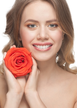 Pretty young woman with beautiful make-up and blond curly hair with rose in her hands Stock Photo - 12797087