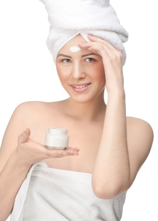 Young beautiful woman in white towel applying moisturizing cream on her face, isolated on white background Stock Photo - 12794880