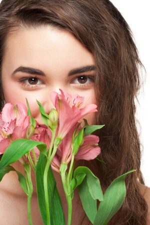 Pretty young woman with beautiful make-up and perfect healthy skin with pink flowers Stock Photo