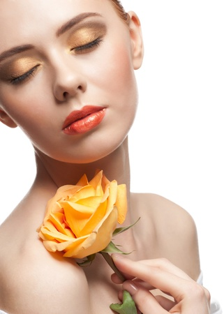 Portrait of young beautiful woman with stylish bright make-up with rose in her hand photo