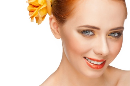 Portrait of young beautiful woman with stylish bright make-up with rose in her hair photo