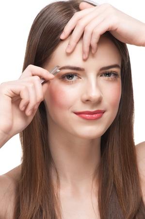 tweezing eyebrow: Young beautiful woman plucking her eyebrows with tweezers. Isolated on white background