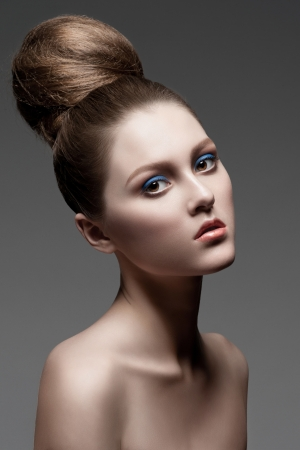 Fashion studio shot of young beautiful woman with stylish makeup and creative hairstyle photo