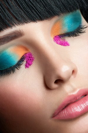 Close-up shot of beautiful woman with bright stylish make-up with closed eyes photo