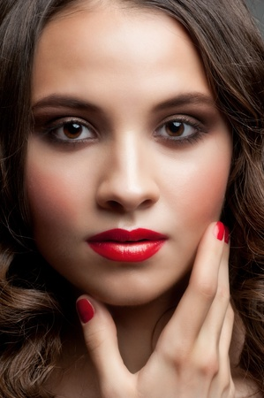 Portrait of young beautiful woman with stylish makeup, hairstyle and red manicure photo