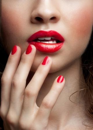 lip shine: Close-up shot delle labbra di donna sexy con rossetto rosso e manicure rosso