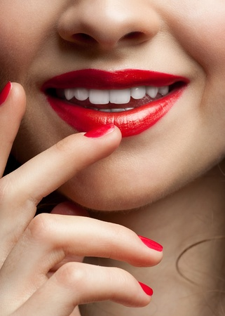 Close-up shot of sexy woman lips with red lipstick and red manicure photo