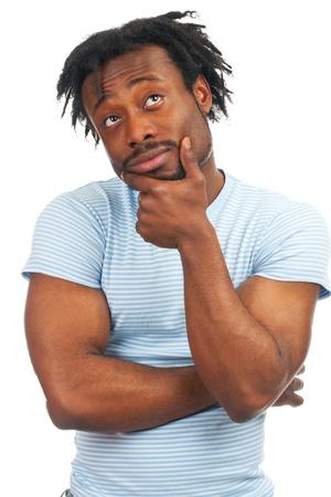 dudas: Retrato de joven pensativa hombre afro-americano mirando hacia arriba, sobre fondo blanco Foto de archivo