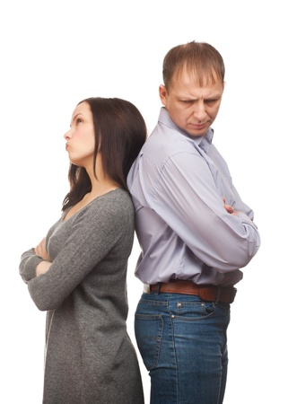 disagree: Young couple standing back to back having relationship difficulties. Isolated on white background