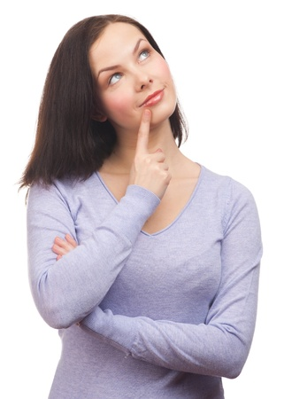 Portrait of  pensive young woman looking up and touching her chin, over white background