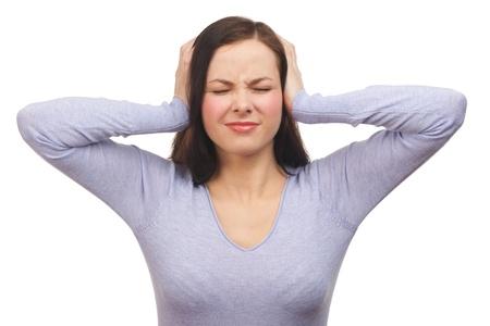 ruido: Retrato de una mujer infeliz joven tapándose los oídos. Aislado sobre fondo blanco