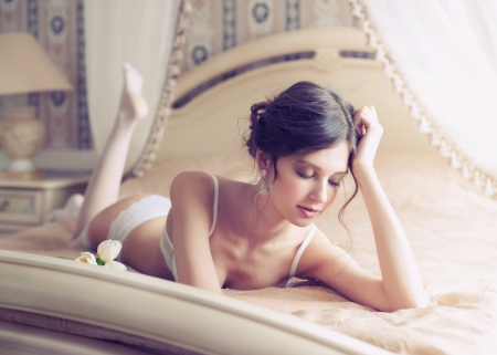 Beautiful bride in white lingerie lying on the bed in her bedroom photo